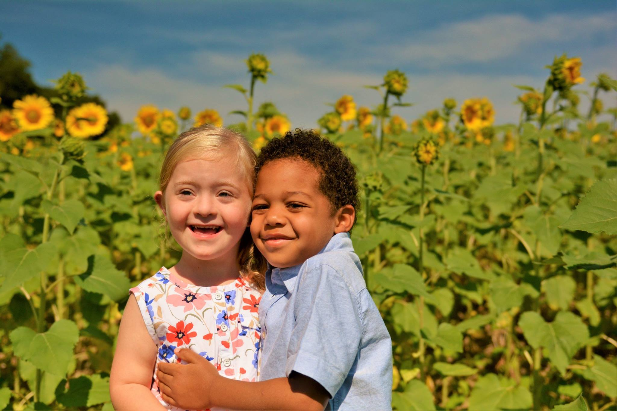 A girl with a developmental disability and her brother in front of a field of sunflowers.